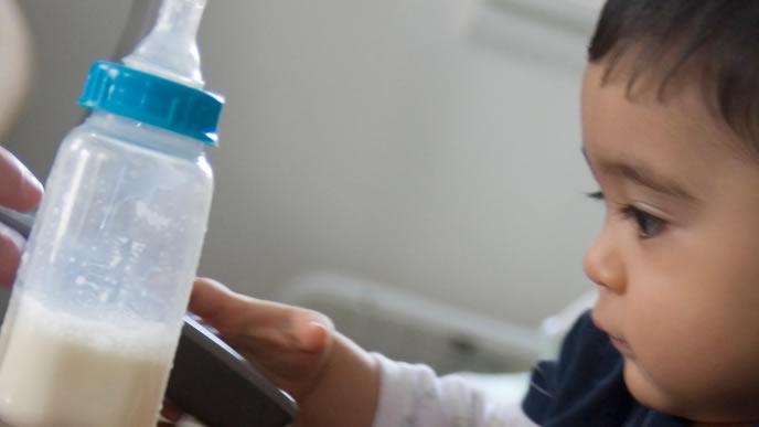 哺乳瓶に入った牛乳に興味がある赤ちゃん
