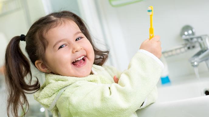 歯ブラシをもって笑顔で歯磨きを始める女の子