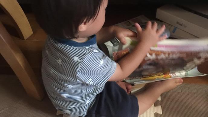お気に入りの本で一人遊びをする赤ちゃん