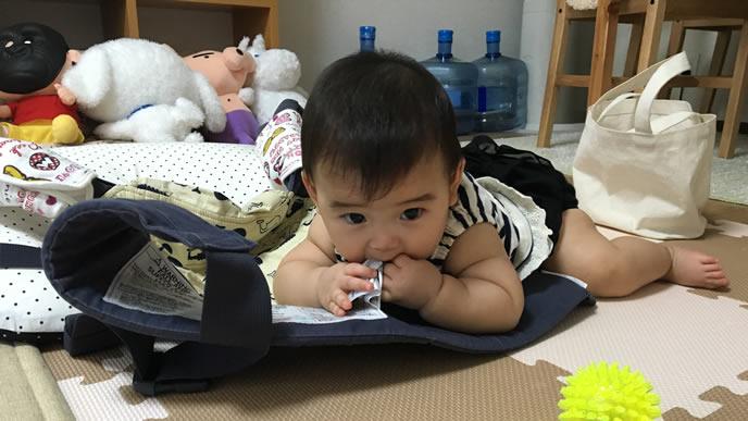 タグを食べる一人遊びをする赤ちゃん