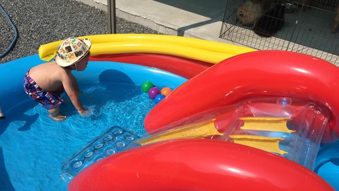 保育園の庭にある家庭用プールで遊ぶ男の子