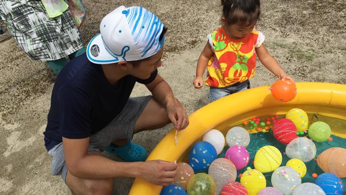 お祭りの縁日でパパと一緒にヨーヨー釣りをする女の子