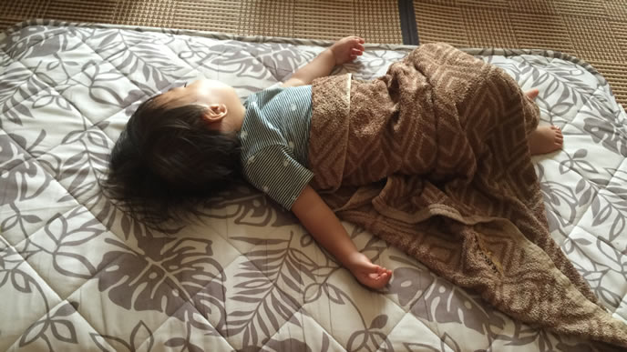 はしゃぎ疲れて毛布に包まり寝る男の子