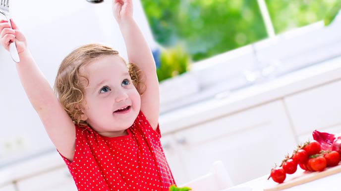両手をあげイチゴを食べる女の子