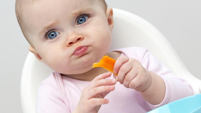 果物を手づかみで食べる赤ちゃん