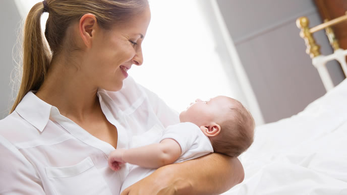 赤ちゃんを抱きあげ優しく見つめるママ
