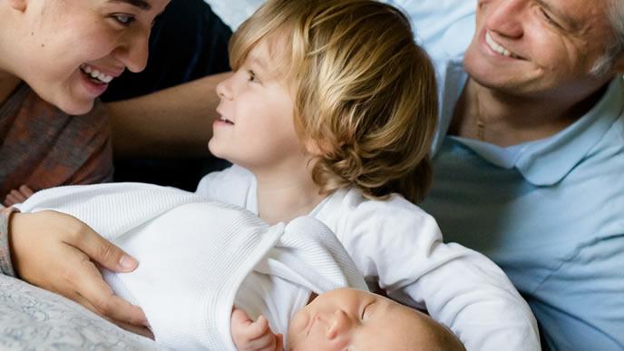 新しく誕生した赤ちゃんを家族にお披露目するママ