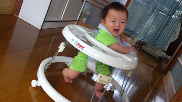 笑顔で歩行器に乗る赤ちゃん