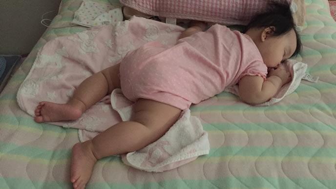 裸足でうつぶせ寝をする赤ちゃん