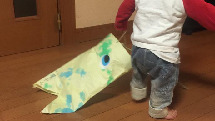 こいのぼりを持って家の中を歩く赤ちゃん