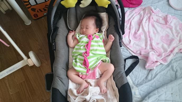 バウンサーで寝ているパジャマを着た赤ちゃん
