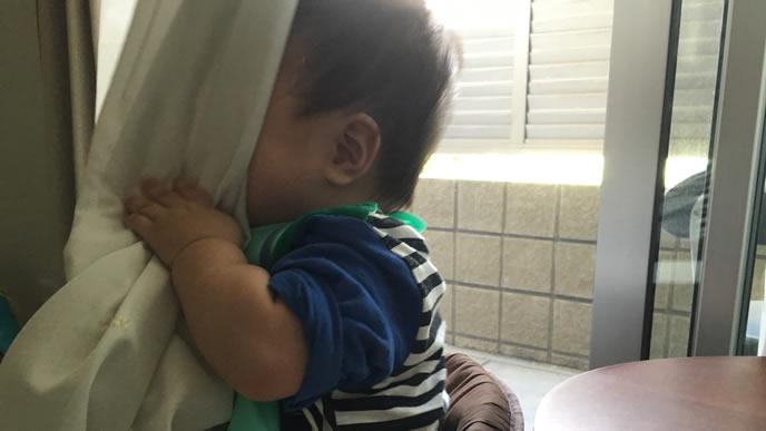 機嫌が悪くなりカーテンの後ろに隠れる赤ちゃん