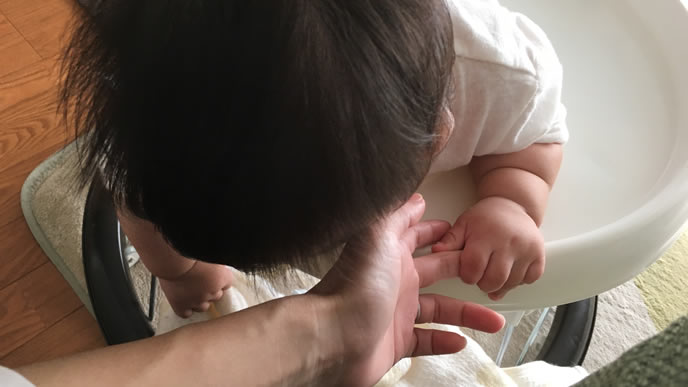 ママと一緒に遊びたくて手を握る赤ちゃん