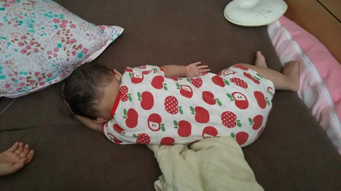 自分の腕をまくらにして横で寝る赤ちゃん