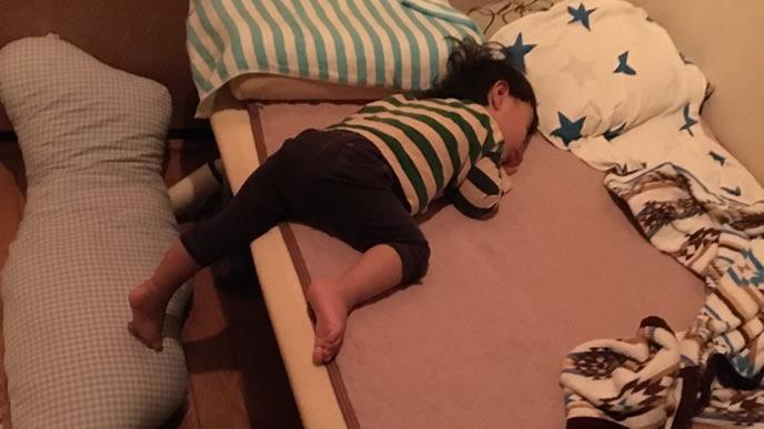 ベッドからはみ出て寝る赤ちゃん