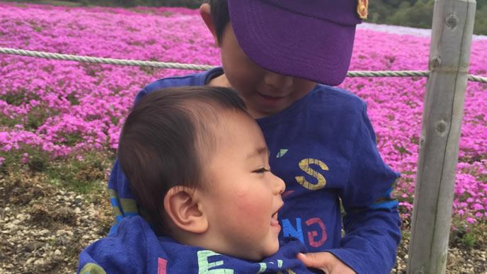 旅行先の花畑で遊ぶ兄と弟
