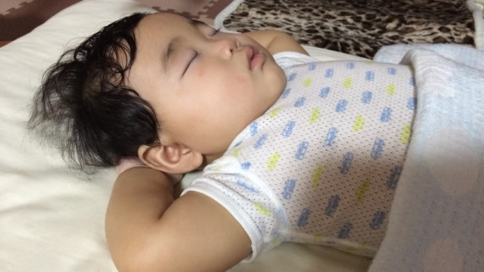 腕を組んで一人寝するネントレが成功した赤ちゃん