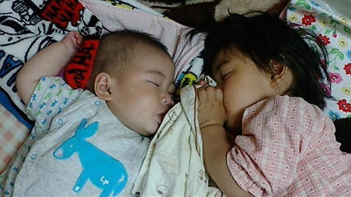姉と一緒に熟睡する赤ちゃん