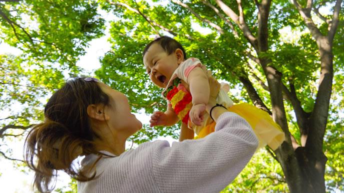 赤ちゃんに高い高いをしてあやすママ