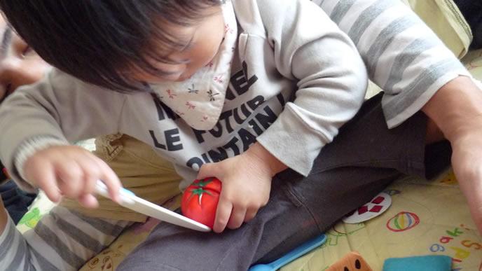 ママごとセットのトマトをスライスしようとする赤ちゃん