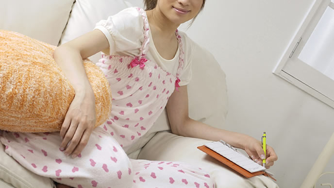 つわりの緩和に適したツボをメモする妊婦
