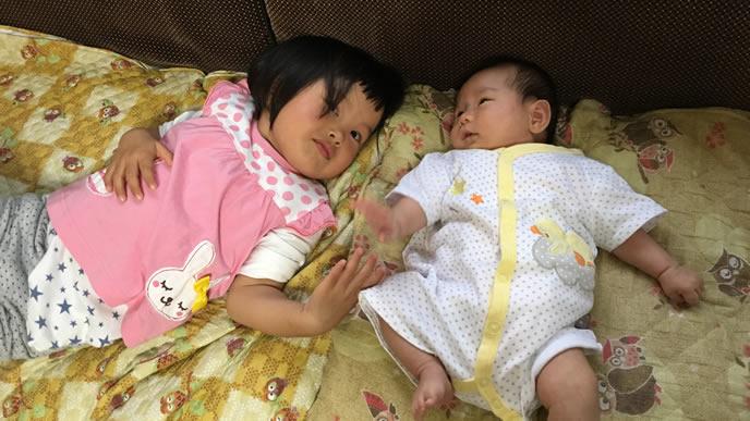 姉と手を握る赤ちゃん