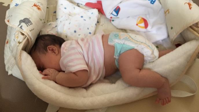 ベビーベッドの端でぐっすり眠る赤ちゃん