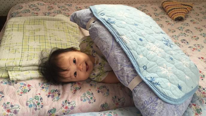 布団の間で笑顔で眠る赤ちゃん