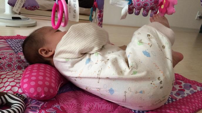 寝返りで宙に向かって足を蹴り上げる赤ちゃん