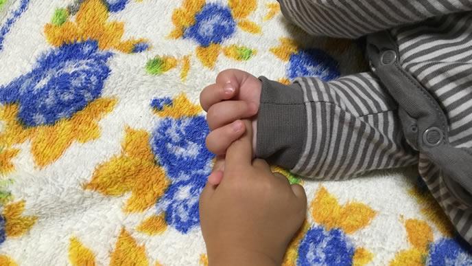 熱が出た不安からママの指を握る赤ちゃん