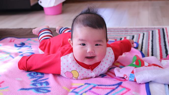 両手を広げてうつ伏せ笑顔の赤ちゃん