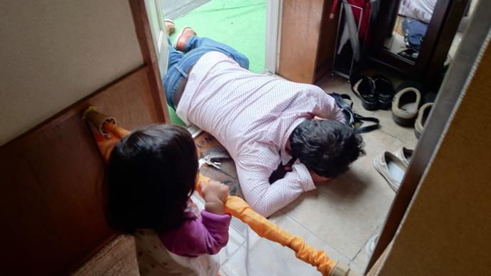 床で寝るパパを観察する女の子