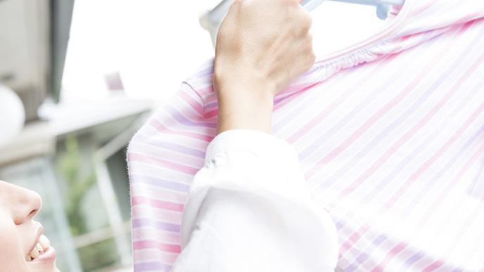 大人と赤ちゃんの洗濯物を干す女性