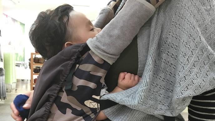 ママにおんぶしてもらうくせっ毛の赤ちゃん
