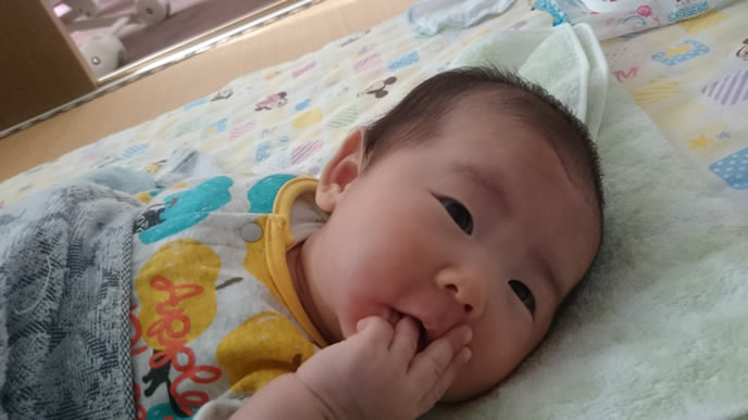 指をなめてママを見つめる赤ちゃん
