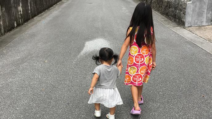 姉に手を引かれお散歩する女の子