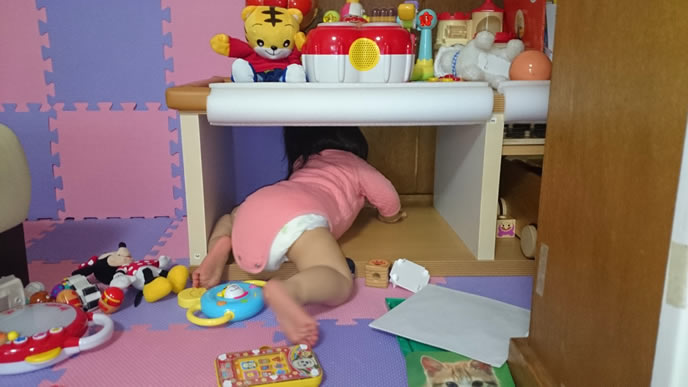 小児科が苦手で棚に隠れようとする赤ちゃん