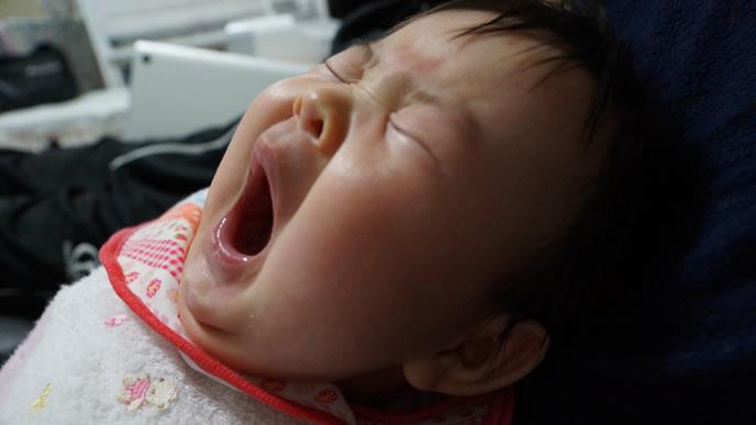 大きなあくびをする眠そうな赤ちゃん