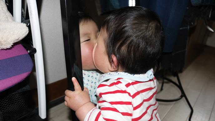 鏡に映った自分にキスをする赤ちゃん