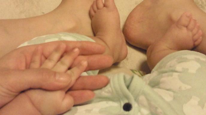 膝の上で赤ちゃんの手を確かめるママ