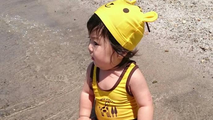 強い日差しから守るためのクマさん帽子を被った赤ちゃん