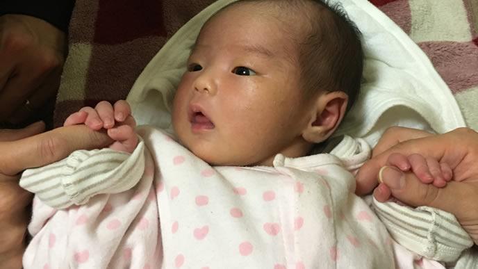 把握反射でママパパの手を握る赤ちゃん