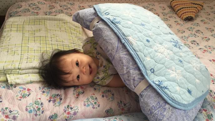 毛布の中から顔を出す伝い歩き時期の赤ちゃん