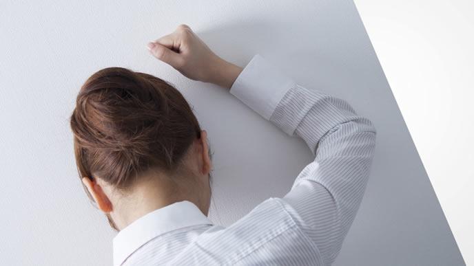 壁に悔しさをぶつける女性