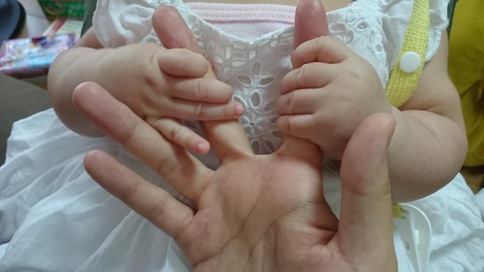 ママの指で楽しく遊ぶ女の子
