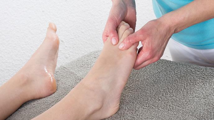 足をマッサージしてこむら返りの予防をする妊婦