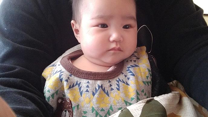 不機嫌な表情で抱っこされる赤ちゃん