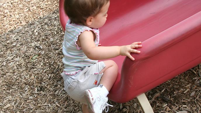 滑り台によじ登る赤ちゃん