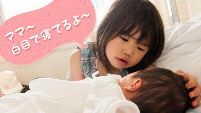 白目を出して寝ている赤ちゃんを心配する女の子