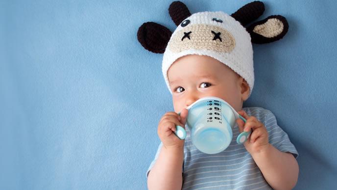 こっちをみて笑顔になる牛さん帽子の赤ちゃん